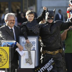 """Miles Scott, dressed as Batkid, second from left, raises his arm next to Batman at a rally outside of City Hall with Mayor Ed Lee, left, and his father Nick and brother Clayton, at right, in San Francisco, Friday, Nov. 15, 2013. Scott was called into service on Friday morning by San Francisco Police Chief Greg Suhr to help fight crime, as San Francisco turned into Gotham City as city officials helped fulfill the 5-year-old leukemia patient's wish to be """"Batkid,"""" The Greater Bay Area Make-A-Wish Foundation says. He was diagnosed with leukemia when he was 18 months old, finished treatment in June and is now in remission, KGO-TV reported. (AP Photo/Jeff Chiu)"""