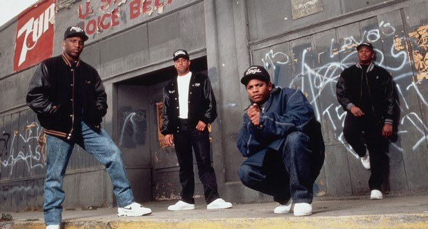 Portrait of members of the rap group, NWA, including DJ Yella, MC Ren, Eazy-E (2nd from right), and Dr. Dre (right), standing in front of an abandoned convenience store. --- Image by © CORBIS