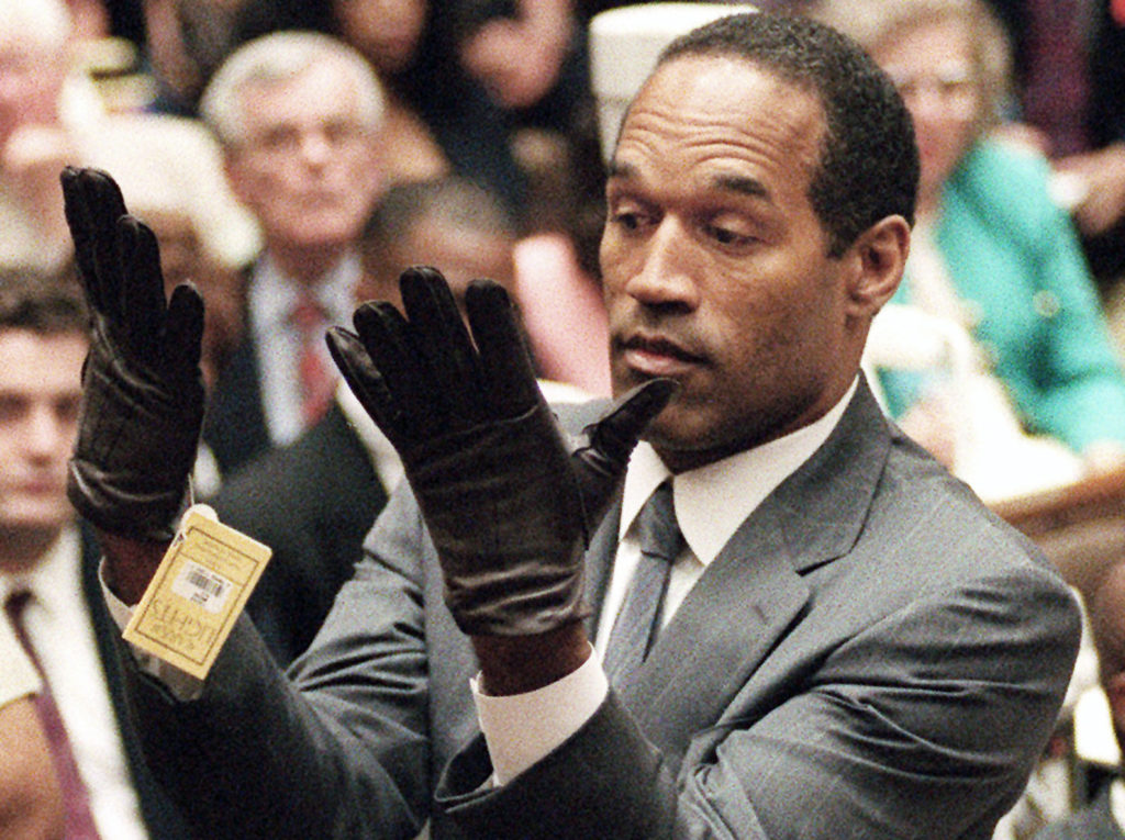 FILE - June 21, 1995 file photo, O.J. Simpson holds up his hands before the jury after putting on a new pair of gloves similar to the infamous bloody gloves during his double-murder trial in Los Angeles. Associated Press writer Linda Deutsch is seen in the background at right; writer Dominick Dunne is in the background at left rear. (AP Photo/Vince Bucci, Pool, File) ** Usable by LA and DC Only **